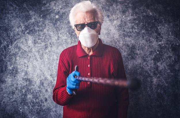 La nonna anziana si protegge dall'infezione da coronavirus con guanti medici e maschera respiratoria