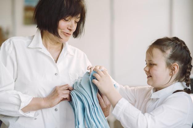 La nonna con la nipotina misura il tessuto per cucire