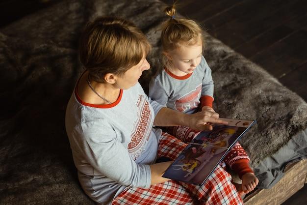 La nonna e la nipote si siedono sul letto in pigiama e libro di lettura.