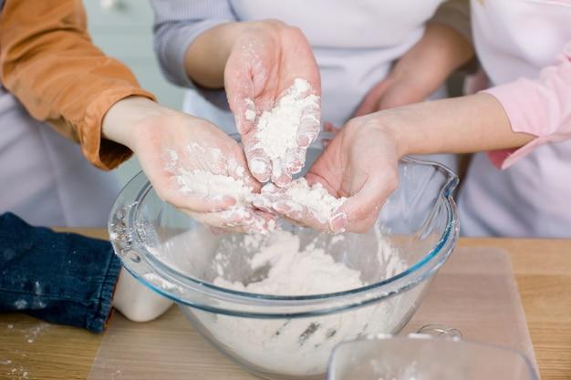 La nonna e le sue figlie tengono la farina nelle loro mani, preparano un impasto nella loro cucina