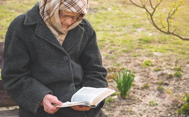 La nonna legge la bibbia delle sacre scritture. pensare a dio