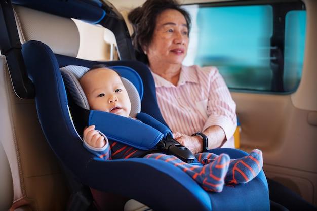 La nonna si prende cura della sua piccola nipotina in macchina, la aiuta e si rallegra