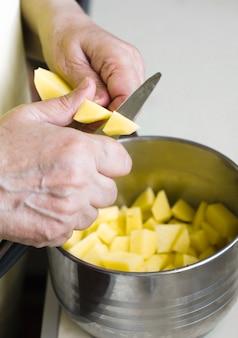 La nonna taglia le patate un coltello in una teglia di metallo