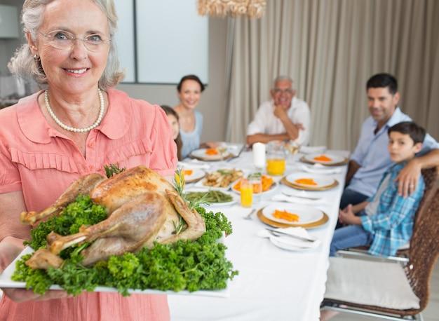 La nonna tiene l'arrosto di pollo con la famiglia al tavolo da pranzo