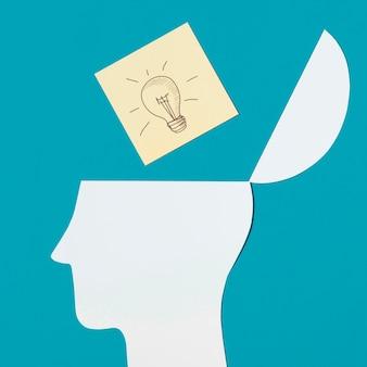 La nota appiccicosa della lampadina sopra la carta aperta ha tagliato la testa contro fondo blu