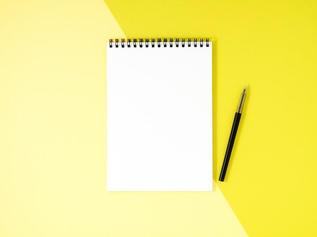 La pagina bianca del blocco note in bianco sullo scrittorio giallo, colora il fondo. vista dall'alto, vuota per il testo.