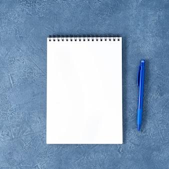 La pagina bianca pulita del blocco note aperto sul tavolo di pietra blu scuro invecchiato, vista dall'alto