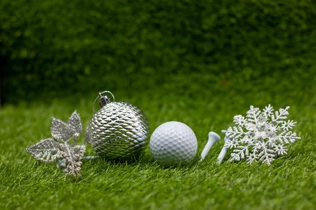 La pallina da golf con il fiocco di neve e l'ornamento di natale sono su erba verde