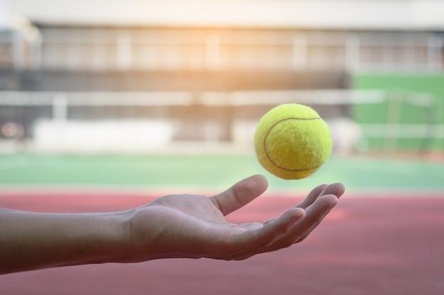 La pallina da tennis sta galleggiando sulla mano e sfoca il fondo della corte