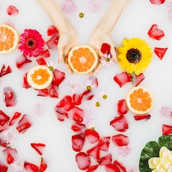 La palma della donna con pompelmo, petali e fiori su chiara acqua bianca