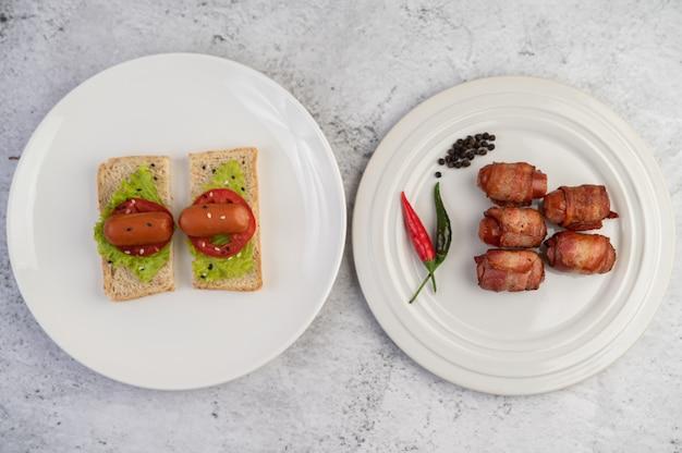 La pancetta di maiale avvolta salsiccia su un piatto bianco e la salsiccia hanno messo sul pane.
