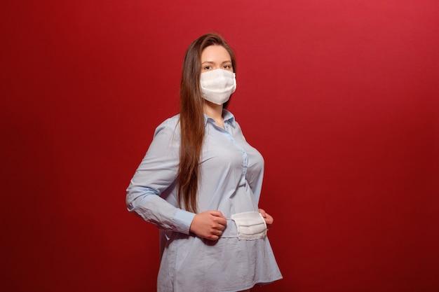 La pandemia di coronavirus, giovane donna incinta su rosso in maschera protettiva medica tiene sullo stomaco