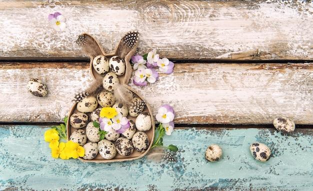 La pansé delle uova di coniglio della decorazione di pasqua fiorisce il fondo