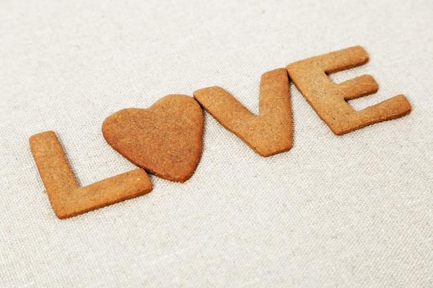 La parola amore dai biscotti allo zenzero su tela di sacco o panno ruvido.