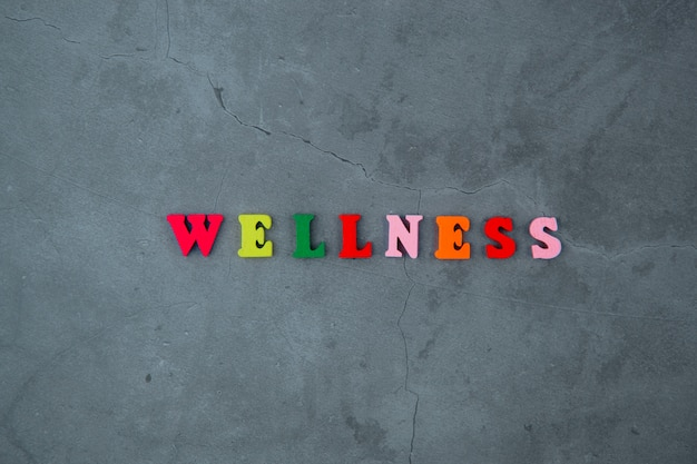 La parola benessere multicolore è fatta di lettere di legno su un muro grigio intonacato.