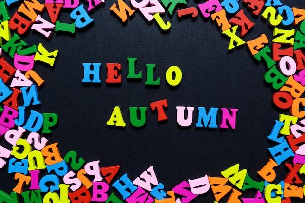 La parola ciao autunno dalle lettere di legno multi-colored su una priorità bassa nera