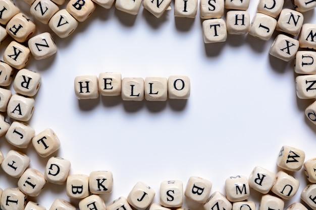 La parola ciao da lettere di legno su uno sfondo bianco