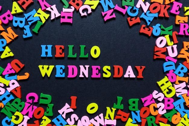 La parola ciao mercoledì dalle lettere di legno multi-colored su una priorità bassa nera