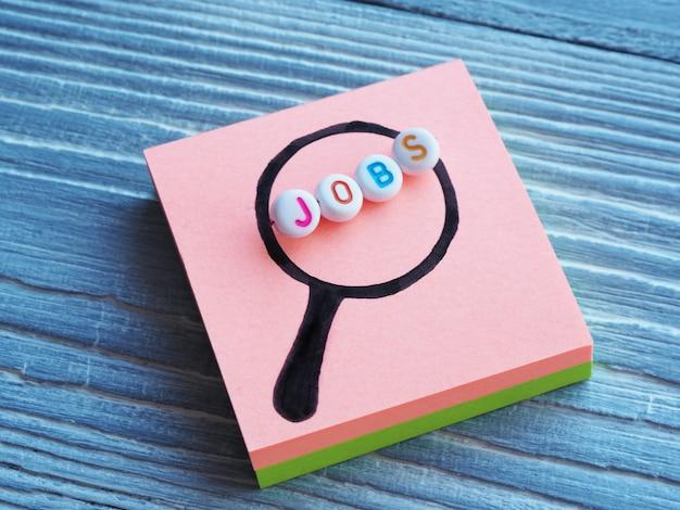 La parola jobs perline di plastica in una lente d'ingrandimento dipinta su uno sfondo di legno. concetto di ricerca di lavoro