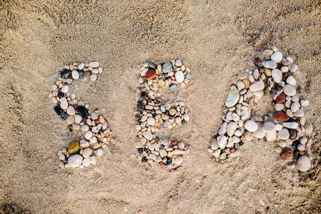 La parola mare di pietre nella sabbia
