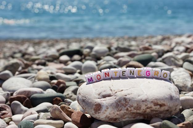 La parola montenegro sui ciottoli sulla riva del mare