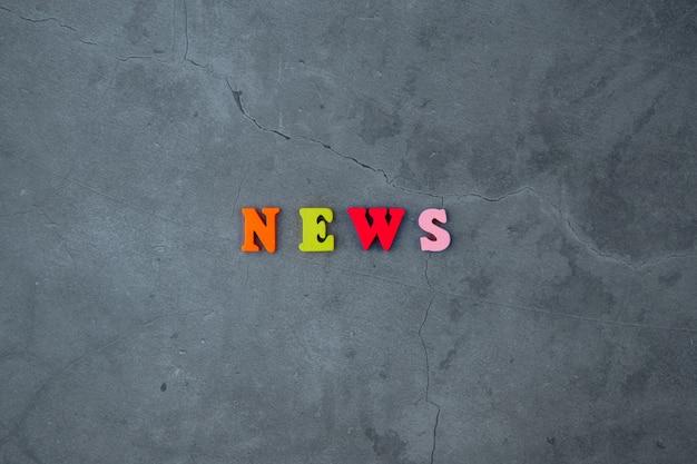 La parola notizia multicolore è fatta di lettere di legno su un muro grigio intonacato.