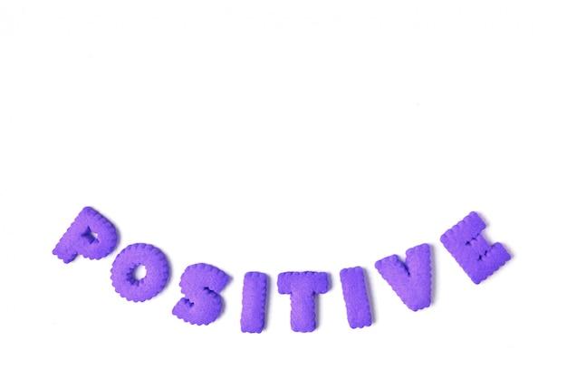 La parola positivo scritto con i biscotti a forma di alfabeto di colore viola su bianco