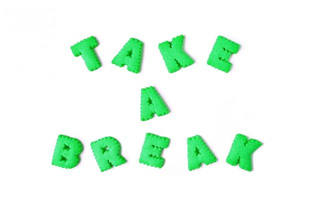 La parola prendilo facile scritto con biscotti a forma di alfabeto di colore verde lime su sfondo bianco