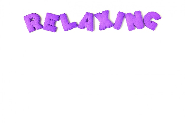 La parola relax scritto con biscotti a forma di alfabeto di colore viola su sfondo bianco
