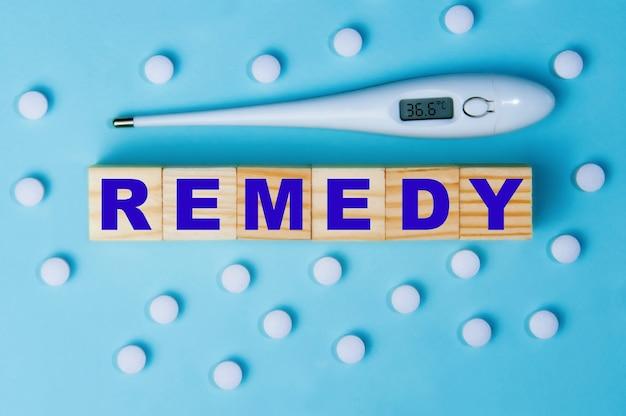 La parola rimedio sui cubi di legno con le pillole e un termometro su un blu.