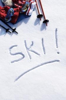 La parola scritta di sci nella neve con racchette da sci