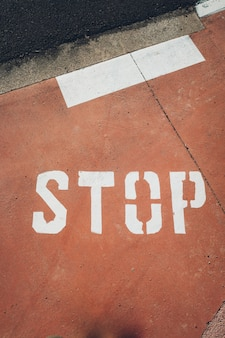 La parola stop dipinta in lettere maiuscole bianche su un pavimento rosso.