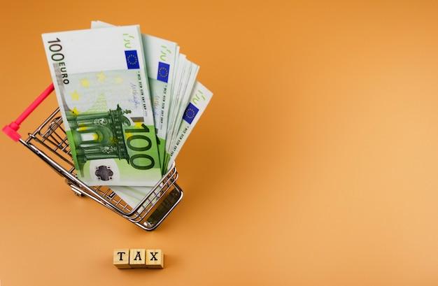 La parola tassa e la valuta dell'unione europea sul carrello dei giocattoli