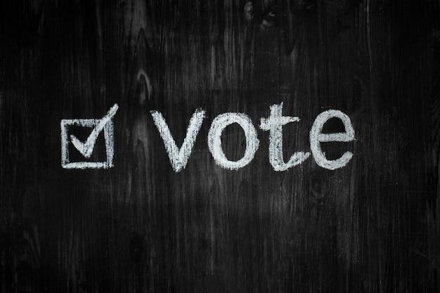 La parola voto e una casella di spunta riempita su una lavagna