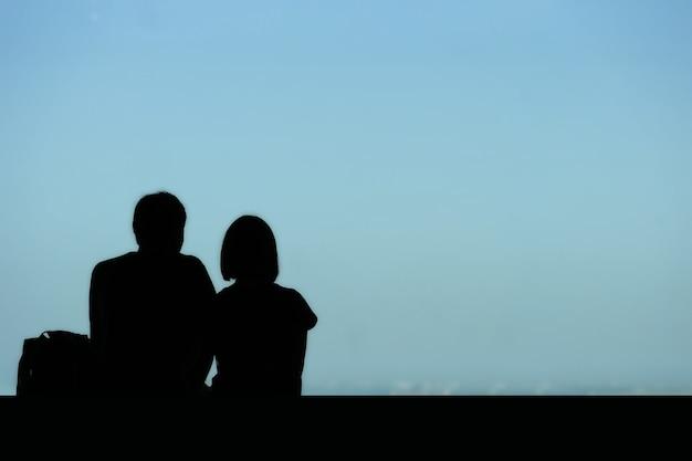La parte di una coppia che guarda la città dall'alta finestra della costruzione.