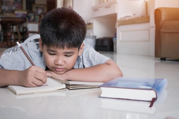 La parte elementare del ragazzo dell'allievo asiatico fa i suoi compiti sul taccuino mentre imparano lo studio