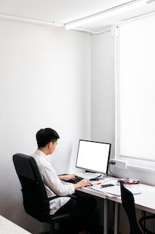 La parte posteriore dell'uomo che porta la camicia bianca e si siede sulla sedia nera dell'ufficio, lavorando con il suo personal computer con esposizione sulla tavola dell'ufficio.