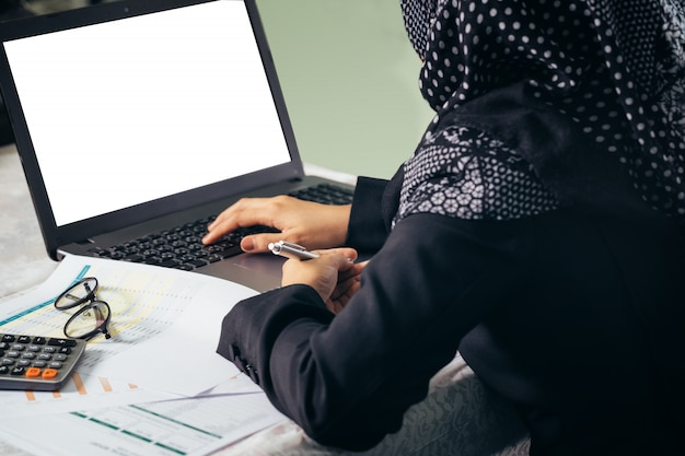 La parte posteriore della donna musulmana di affari che lavora display portatile vuoto.