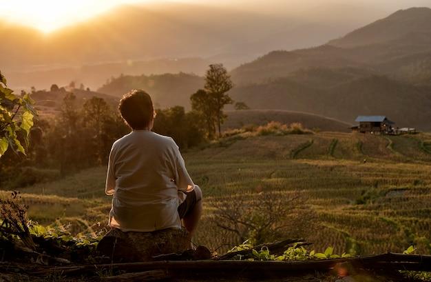La parte posteriore della donna senior che guarda il campo di riso di vista vicino alla montagna a mae chaem
