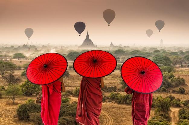 La parte posteriore di tre novizi buddisti sta camminando sopra gli antichi templi di bagan