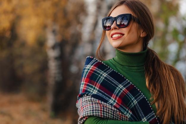 La passeggiata alla moda accogliente della ragazza al parco variopinto di autunno in occhiali da sole