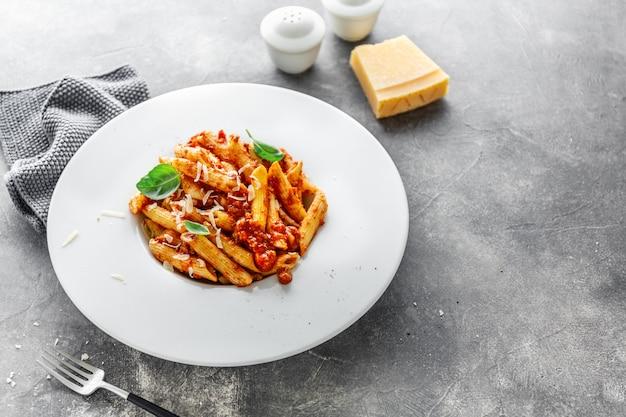 La pasta alla penne bolognese è servita sul piatto