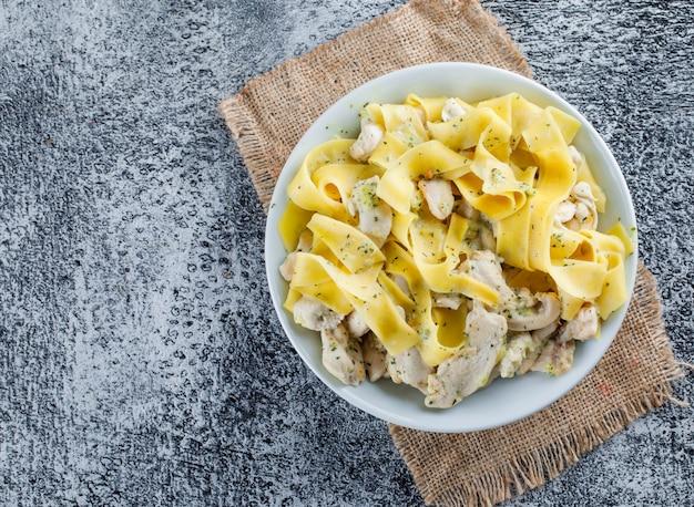 La pasta con carne in un piatto piatto giaceva su grungy e pezzo di sacco