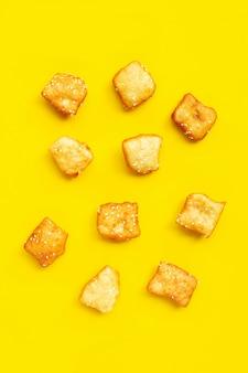 La pasta fritta nel grasso bollente cinese attacca con i semi di sesamo bianchi.