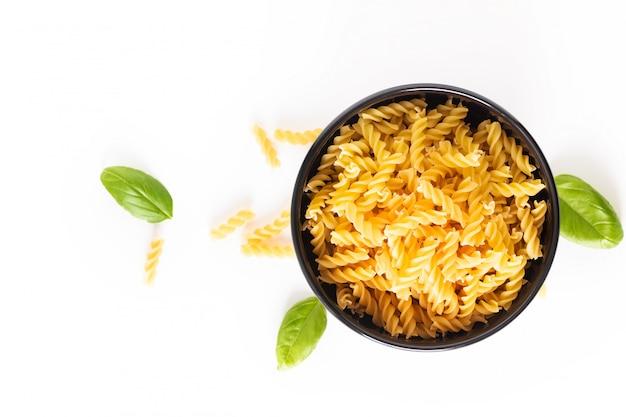 La pasta italiana organica cruda di fusili di concetto dell'alimento in ciotola nera isola su bianco con lo spazio della copia