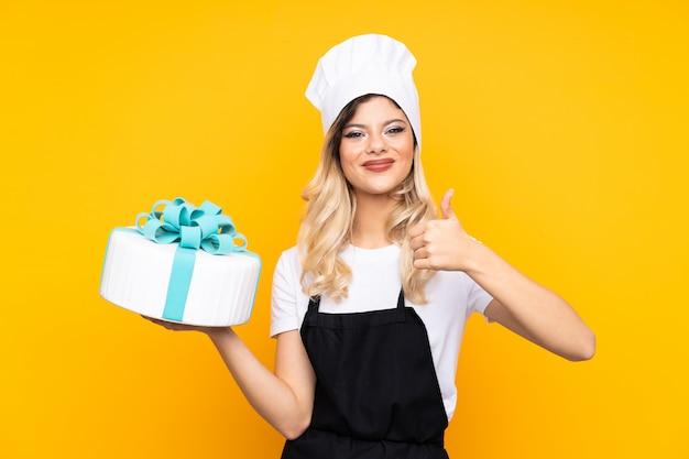 La pasticceria della ragazza dell'adolescente che tiene un grande dolce sulla parete gialla che dà pollici aumenta il gesto