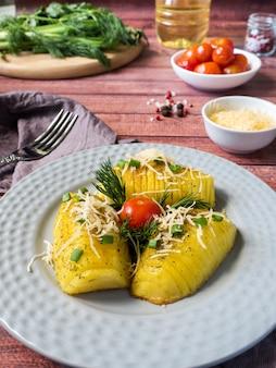 La patata al forno con i pomodori delle verdure condisce il prezzemolo della cipolla verde sul piatto