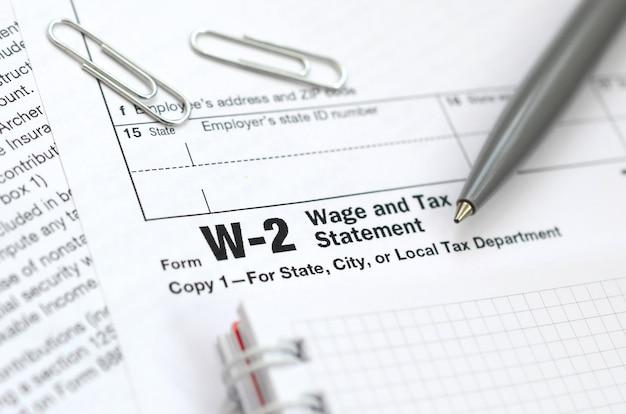 La penna e il taccuino sul modulo fiscale w-2 salario e dichiarazione dei redditi. il tempo di pagare le tasse