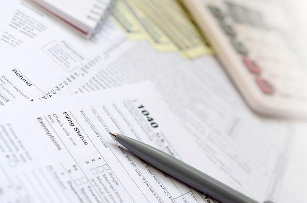 La penna, il taccuino, la calcolatrice e le banconote in dollari si trovano nel modulo fiscale 1040 us imposta sul reddito delle persone fisiche.