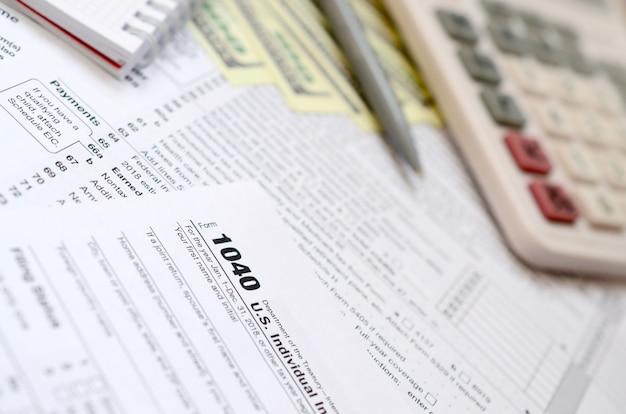 La penna, taccuino, calcolatrice e banconote da un dollaro è bugie sul modulo fiscale 1040 stati uniti